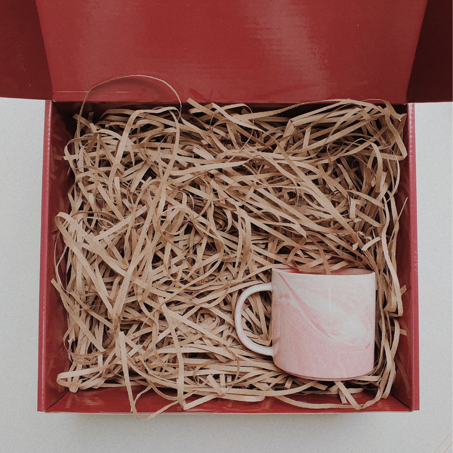 Red gift box filled with brown shredded paper. On the bottom right is a pink marbled mug with handle.