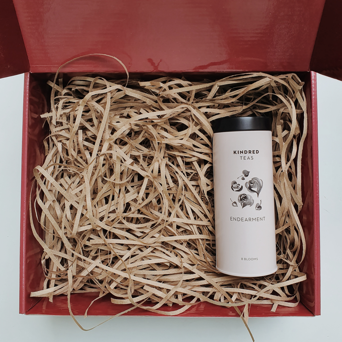 Red gift box filled with brown shredded paper. On the right is a pink cylindrical tin can with black lid. The tin can is labeled Kindred Teas on top, with flowers in the middle and the words Endearment and 8 blooms below.
