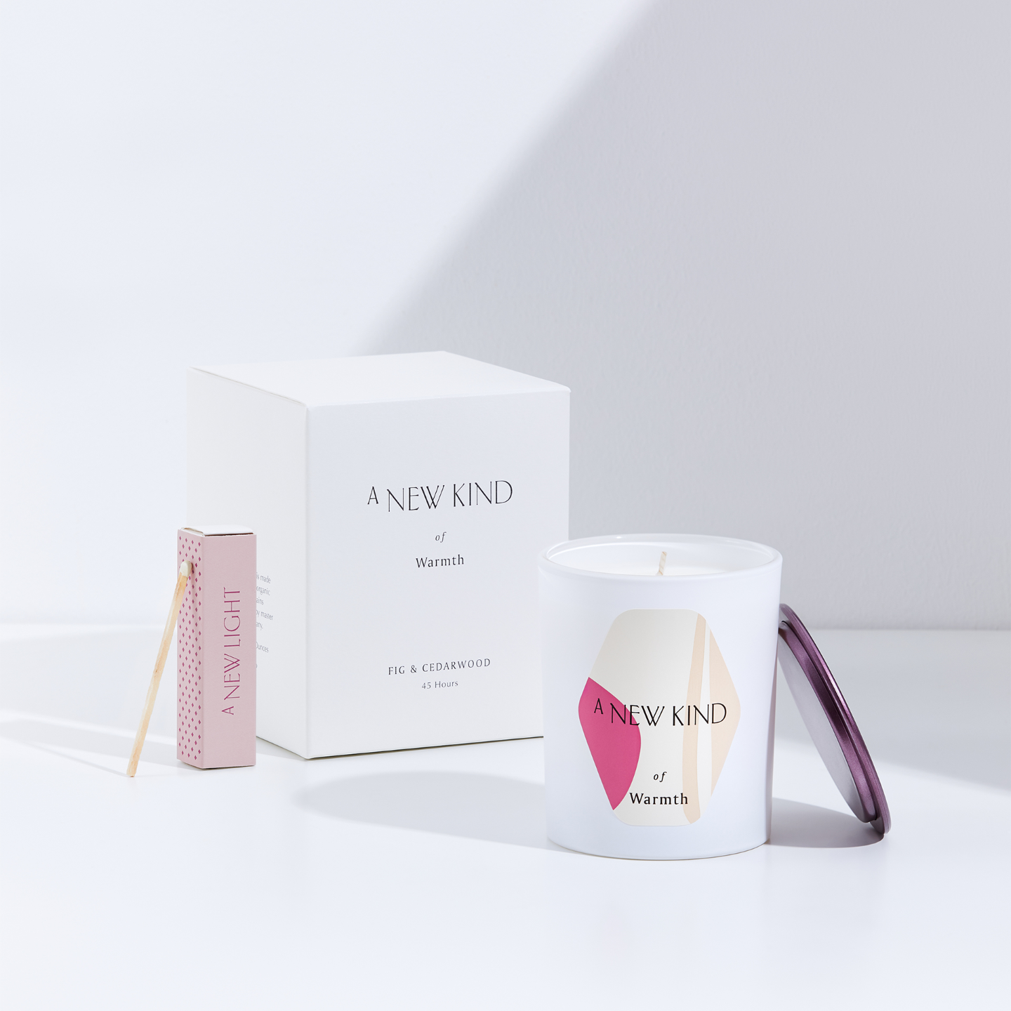 A white candle in the foreground with a pink cover leaning against it and a white candle box in the background with a pink match box beside it. The candle is labeled with a hexagon sticker. The sticker has a white base with abstract prints in pink and beige. The words A new kind of warmth is printed on it. The same words can be seen on the white box behind.