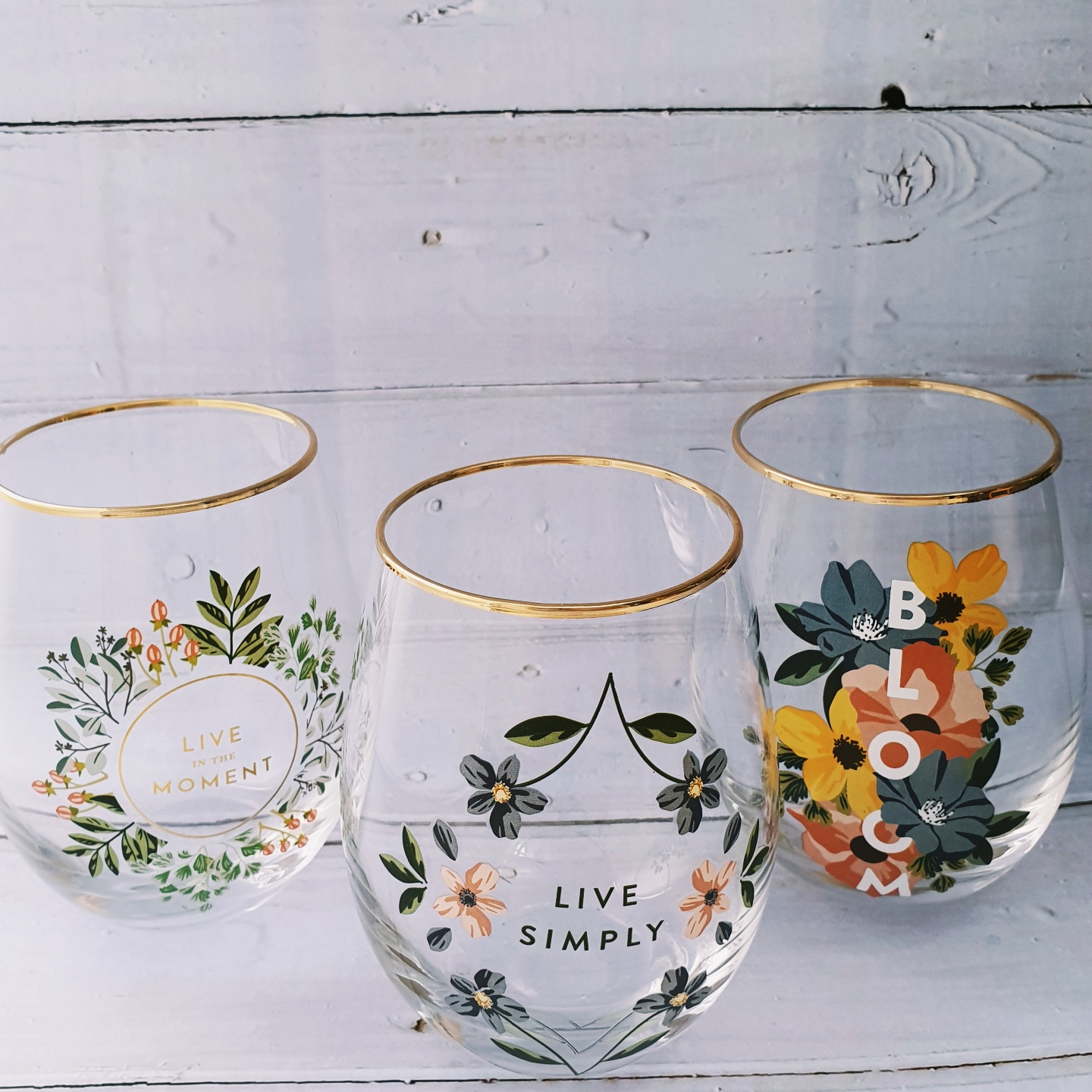 Three stemless wine glasses with gold rim. The wine glass on the left says  Live in the moment and is decorated by a pink and blue floral wreath. The wine glass in the middle says  Live Simply and is decorated by pink and blue flowers. The wine glass on the right says Bloom and is decorated with huge yellow, blue and red flowers.