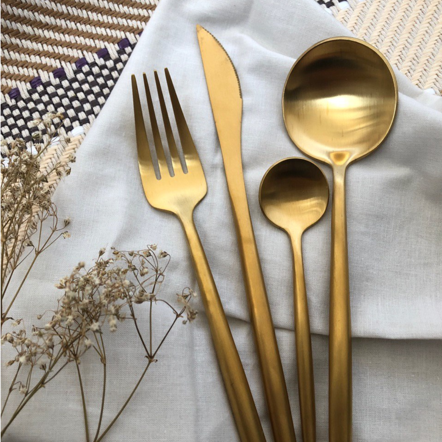 A set of gold cutlery containing a tea spoon, spoon, fork and knife.