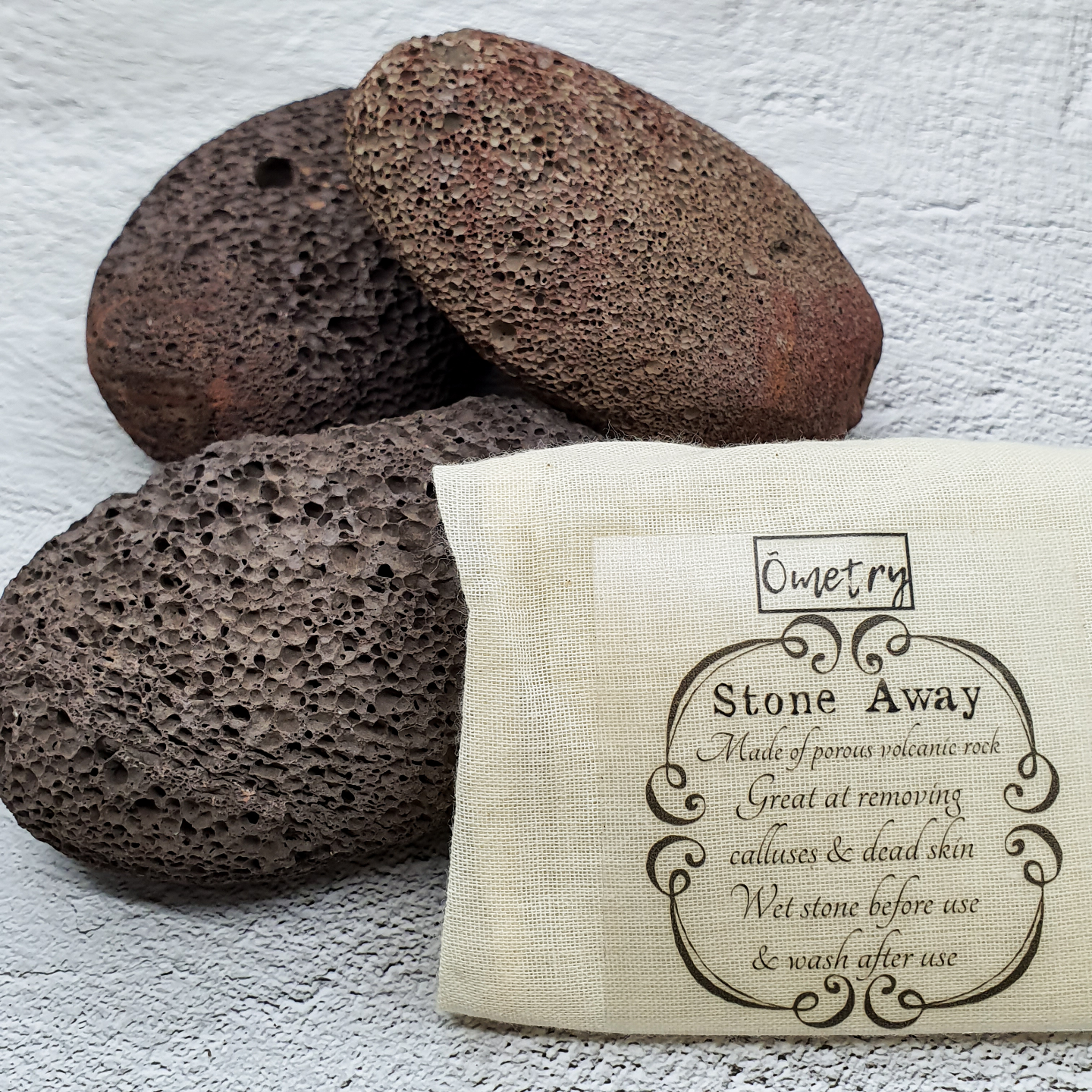 A light brown drawstring pouch with the words Ometry printed above and Stone away printed below.