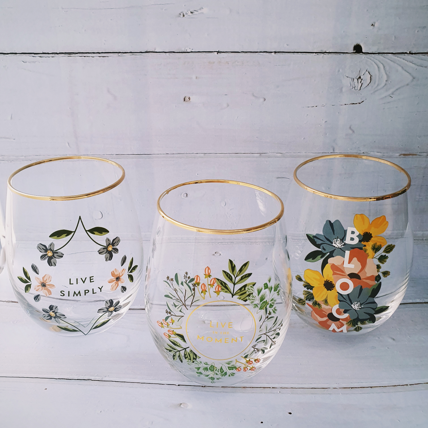 Three stemless wine glasses with gold rim. The wine glass on the left says Live Simply and is decorated by pink and blue flowers. The wine glass in the middle says Live in the moment and is decorated by a pink and blue floral wreath. The wine glass on the right says Bloom and is decorated with huge yellow, blue and red flowers.