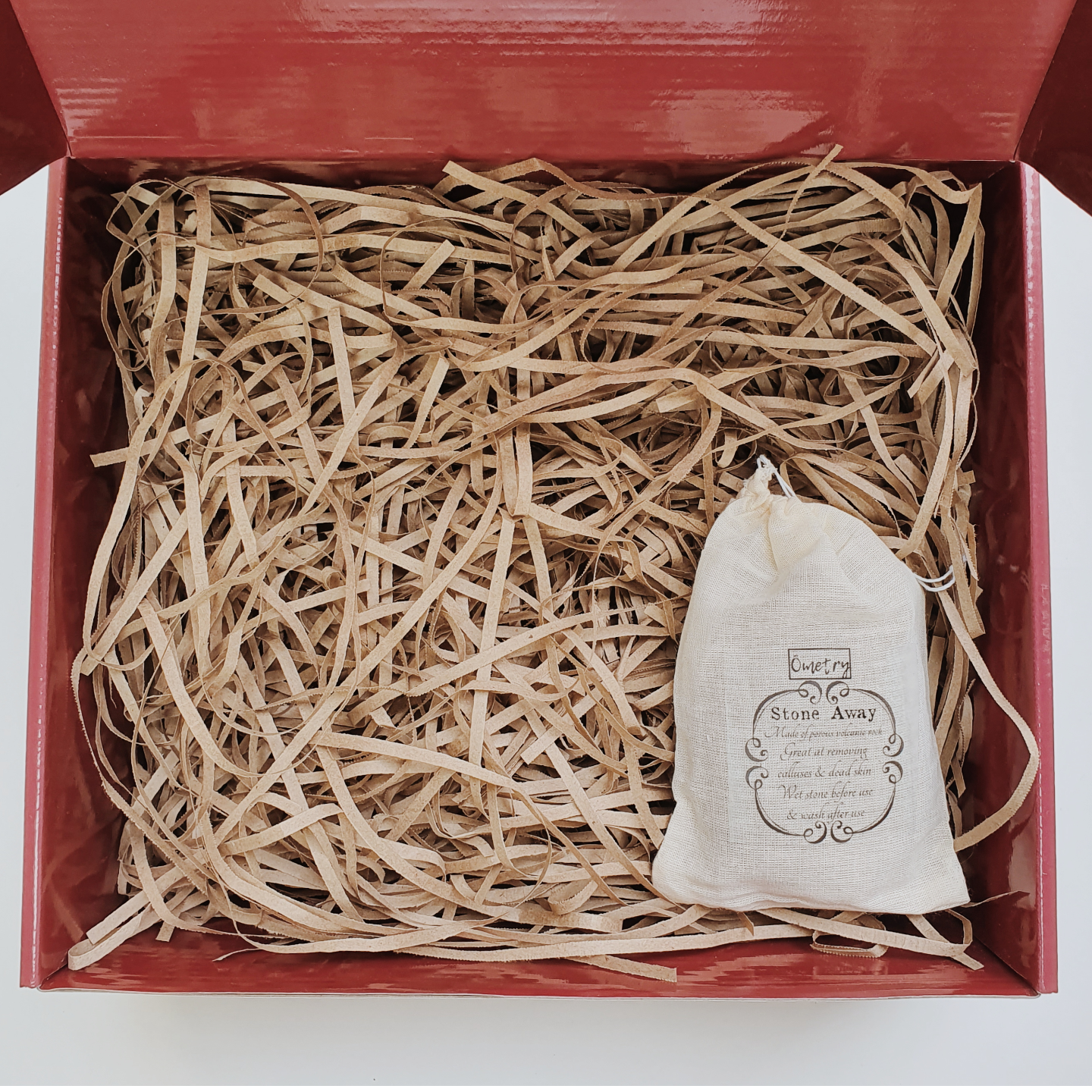 Red gift box filled with brown shredded paper. On the bottom right is a light brown drawstring pouch with the words Ometry printed above and Stone away printed below.