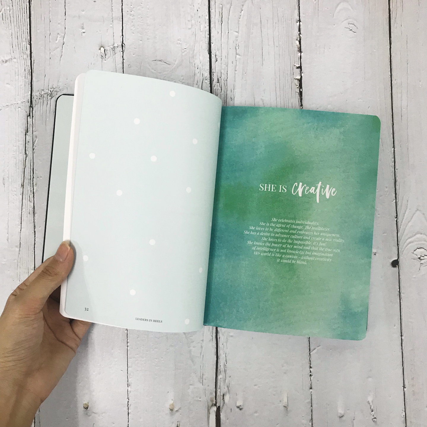 A hand flipping through a journal. The left page is blank with a light blue background and white polka dots while the right page has a green watercolour background with the words You are creative.
