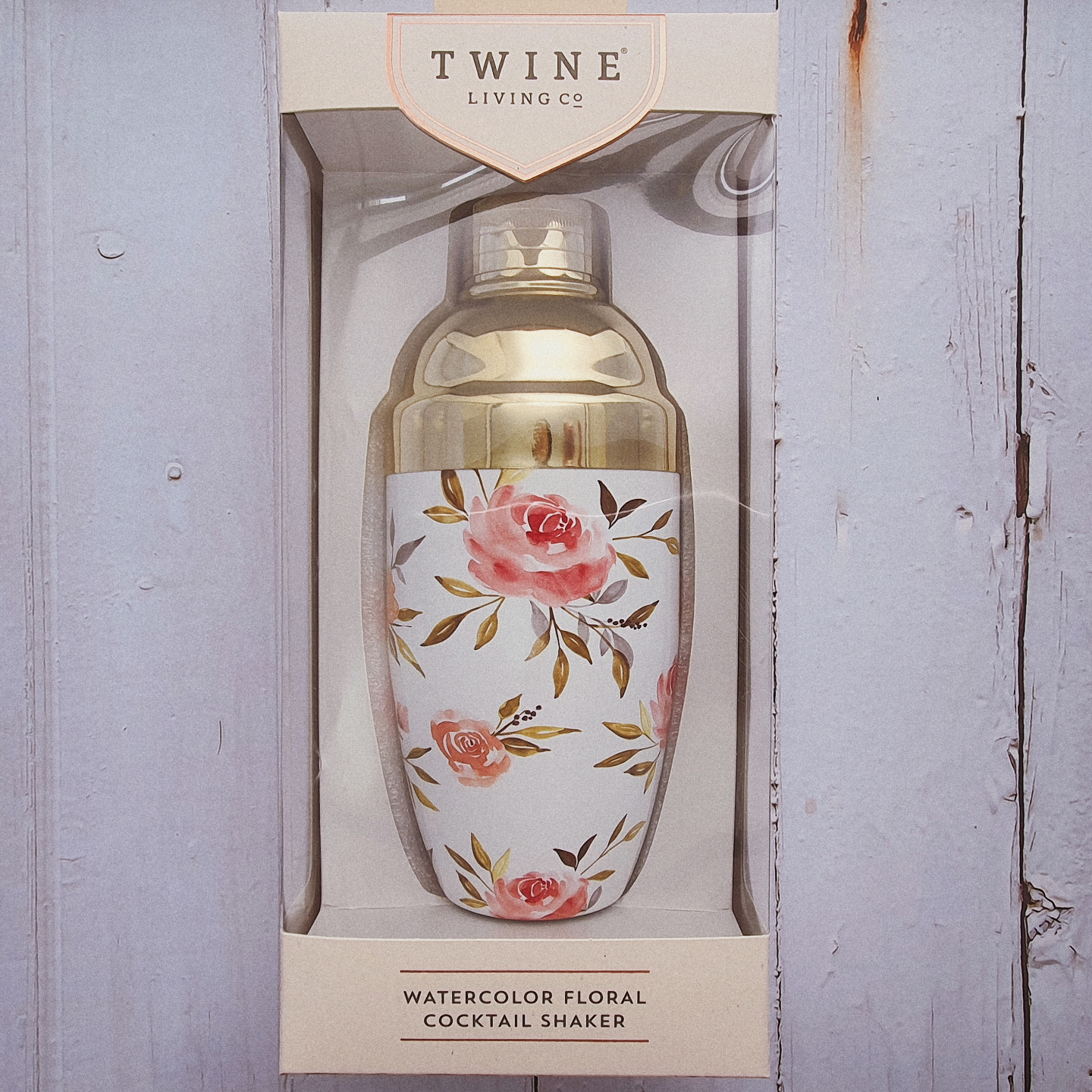 A gold cocktail shaker with watercolour floral prints on its body, packaged in a see through box.