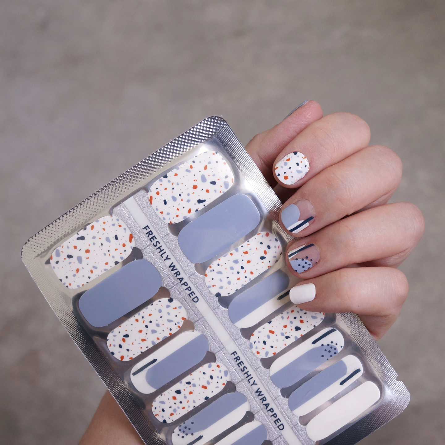 A female left hand holding on to a nail wrap in clear plastic packaging. The nail wrap comes in five different design for each nail. The nail for the thumb is in baby blue, while the index finger has a white base with terrazzo pattern in orange, baby blue and dark blue. The middle finger has a transparent base with two blob shapes in light blue and white emerging from the tip of the nail. A dark blue vertical line cuts through the white blob shape. The ring finger has a clear base with two blob shapes in light blue and white. A dark blue vertical line cuts through the white blob and dark blue dots are found on the light blue blob. The baby finger is in white. The hand also has the nail wrap on her finger nail.