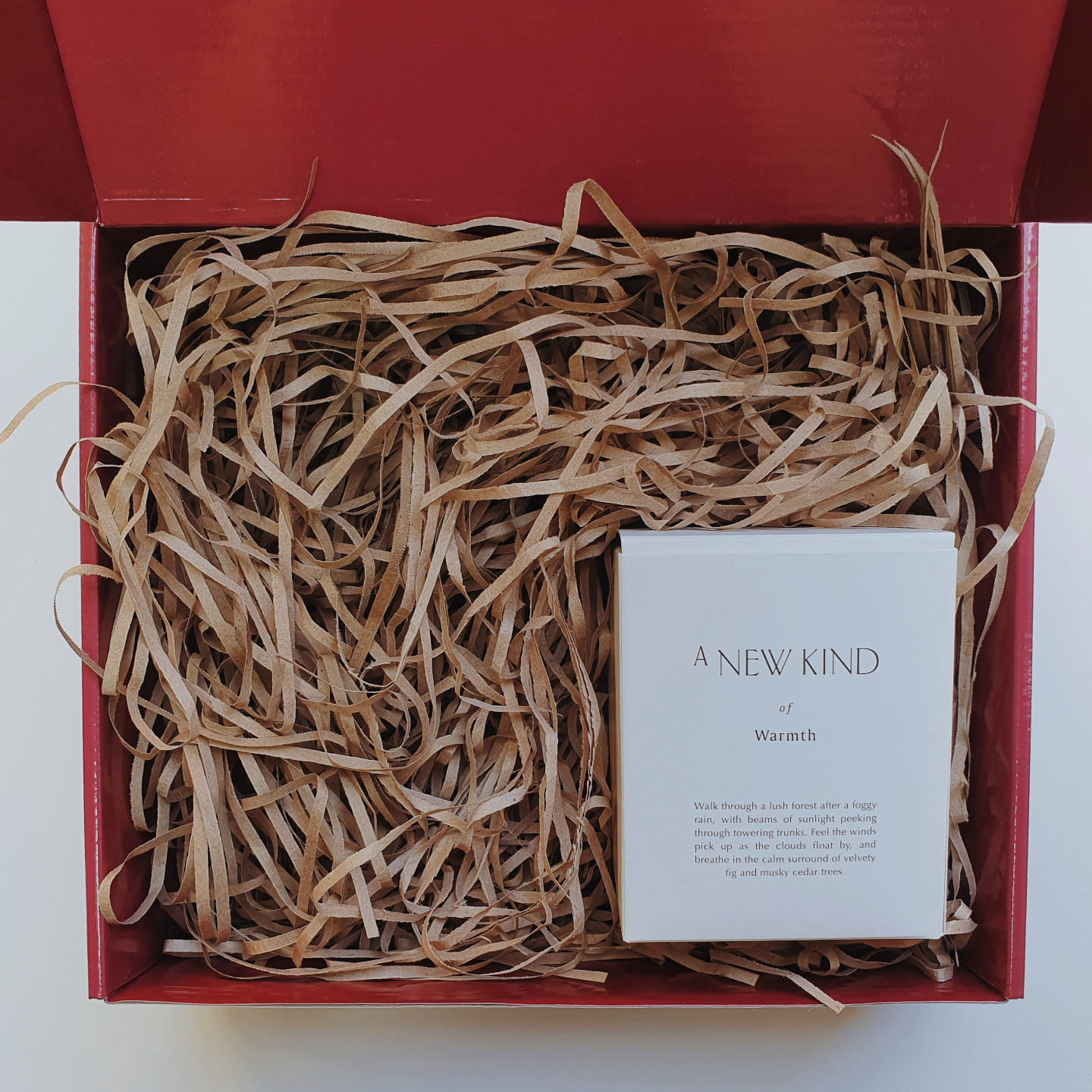 Red gift box filled with brown shredded paper. On the bottom right is a white box with the words A new kind of warmth printed on it.