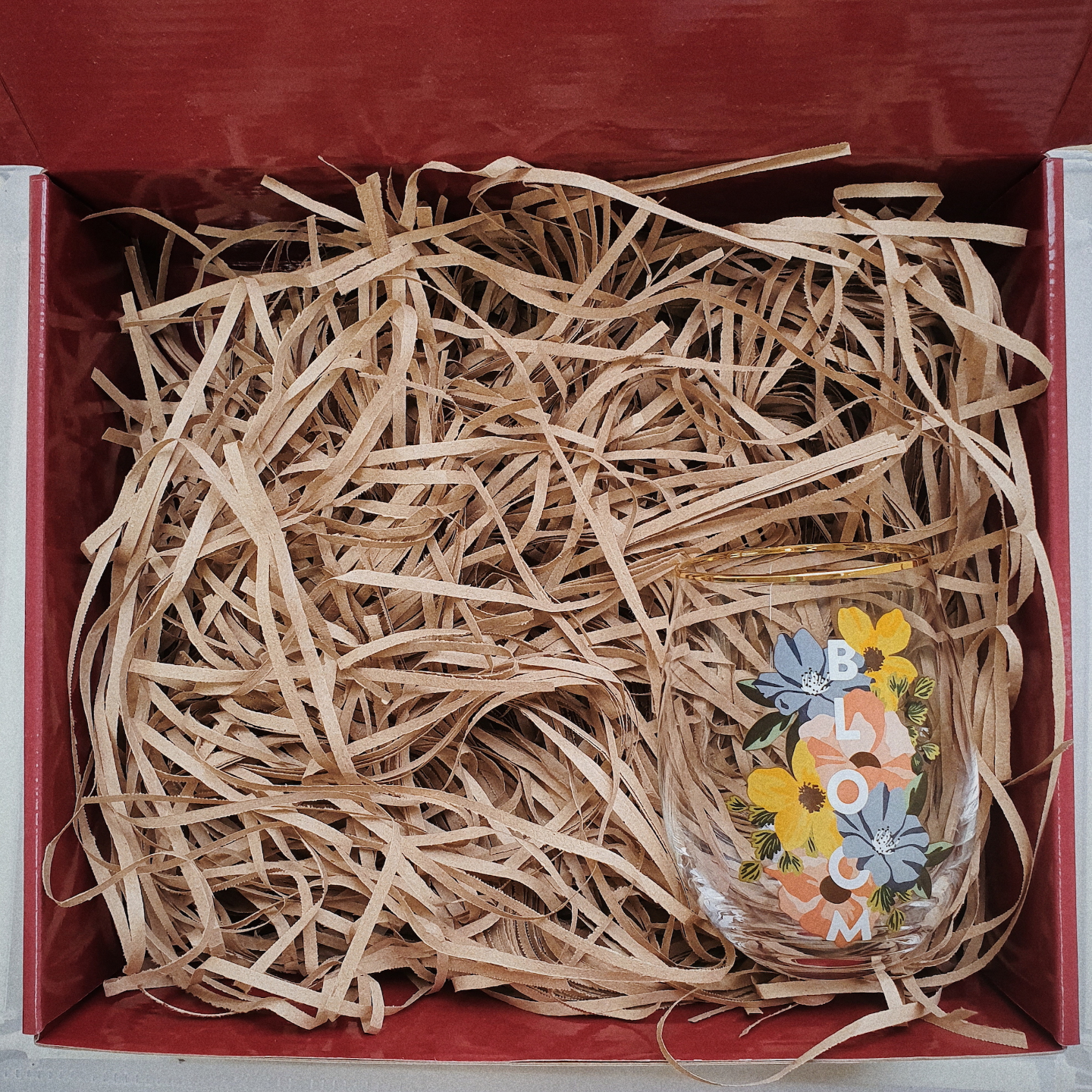 Red gift box filled with brown shredded paper. On the bottom right is a gold rimmed stemless wine glass which says Bloom in caps and is decorated by huge yellow, red and blue flowers.