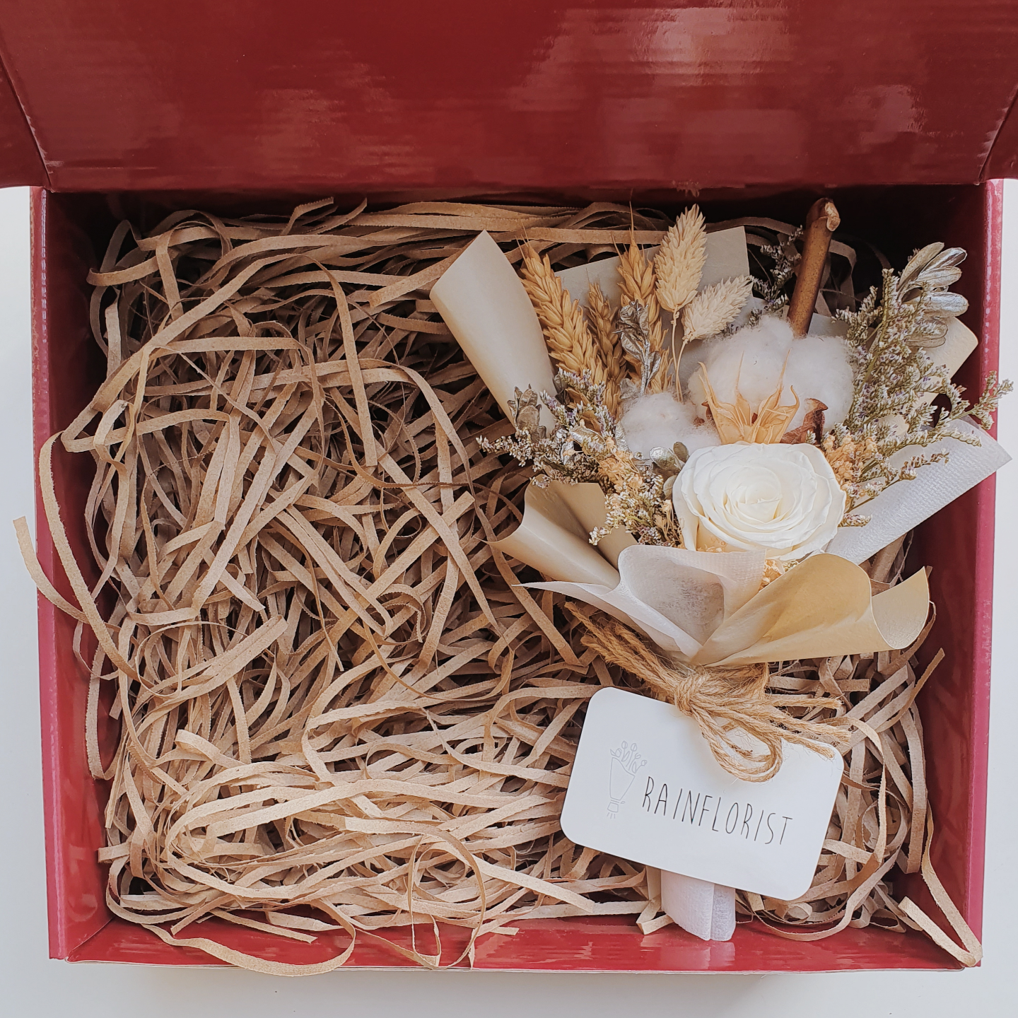 Red gift box filled with brown shredded paper. On the right is a bouquet of dried flowers in coffee brown.