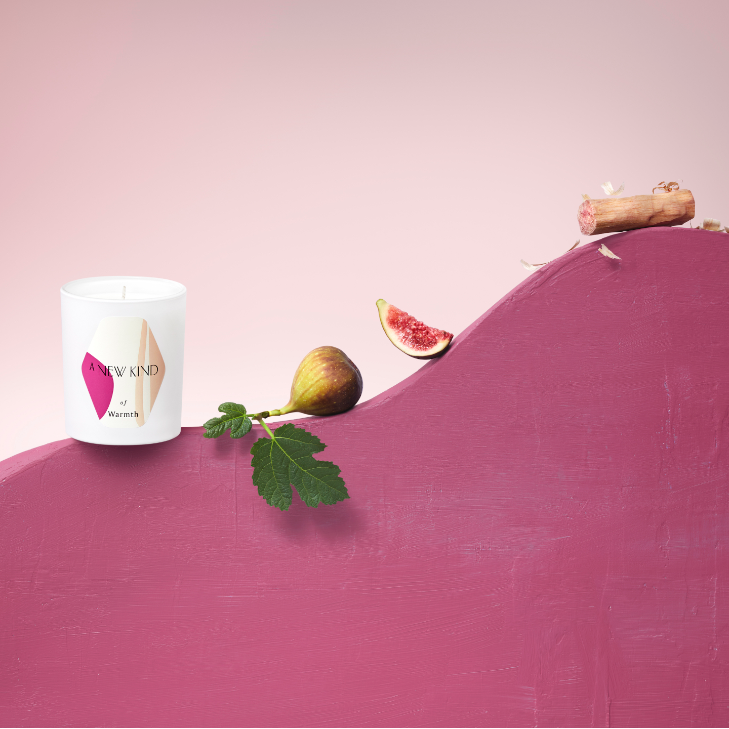 A white candle labeled with a hexagon sticker. The sticker has a white base with abstract prints in pink and beige. The words A new kind of warmth is printed on it.